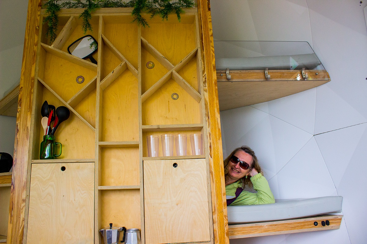 Interior of suspended sleeping pod, includes tiny kitchen and elevated beds.