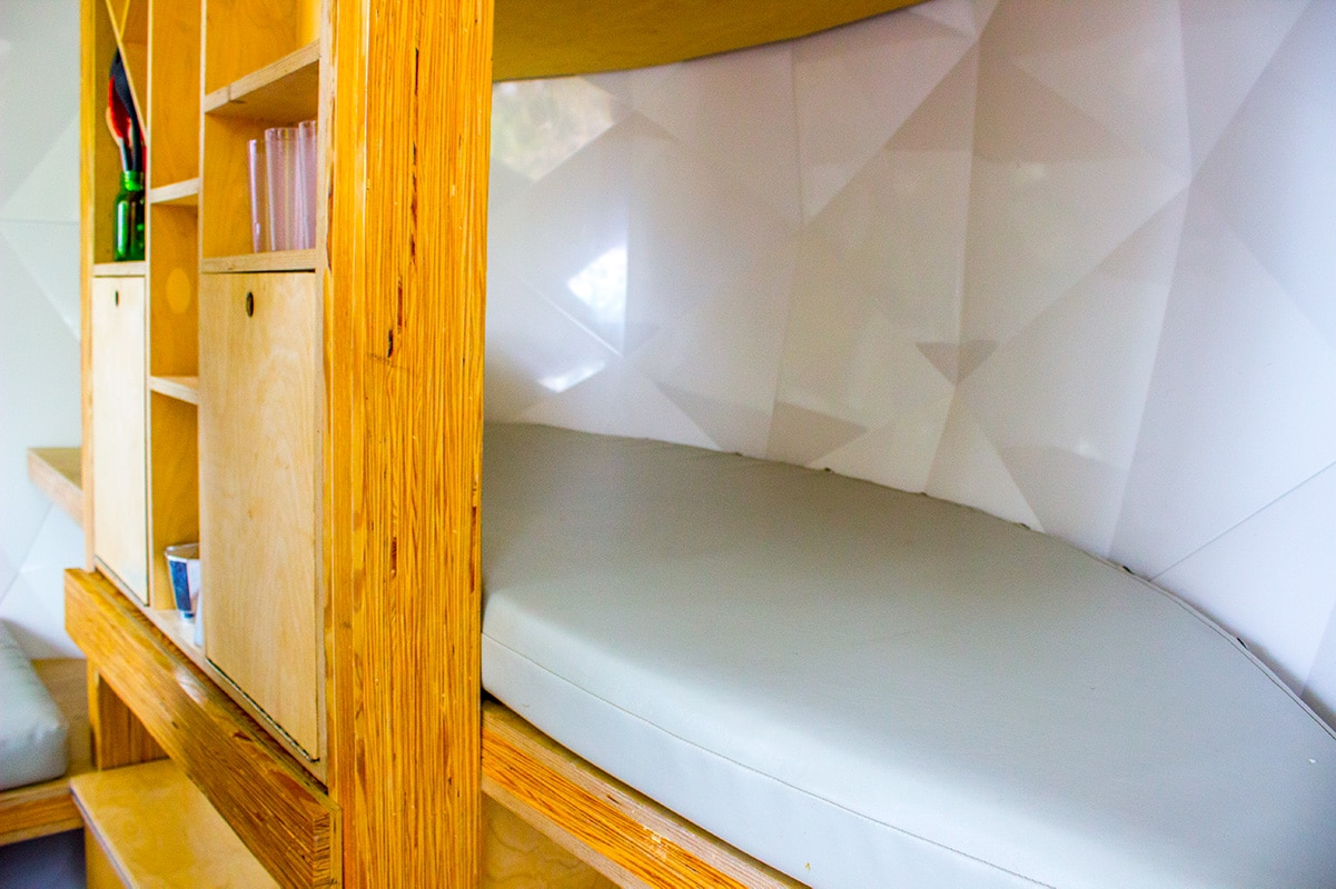 Interior of camouflaged suspended pod, includes tiny kitchen and room for three to four guests.